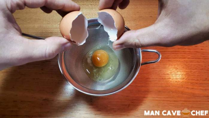 Crack egg into strainer